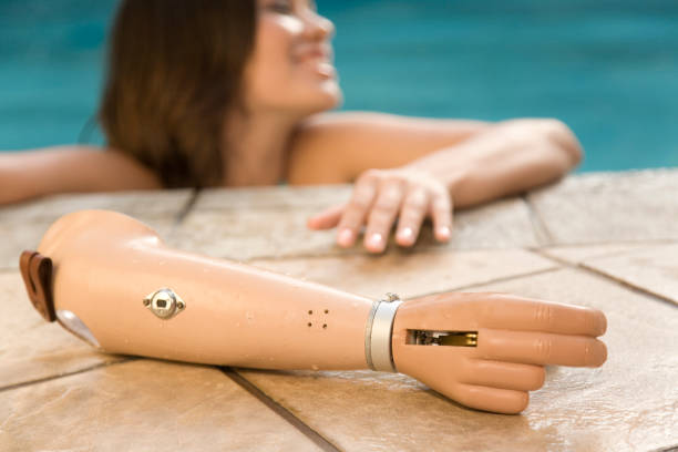 Young Woman with a Prosthetic Arm  prosthetic hand stock pictures, royalty-free photos & images