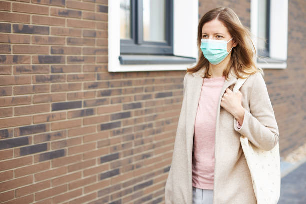 a young woman with a respirator or surgical mask leaves the house - indumento sportivo protettivo foto e immagini stock