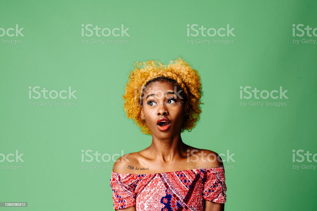 Young woman with a shocked expression looking at something, isolated on green studio background Young woman with a shocked expression looking at something Abundance Stock Photo