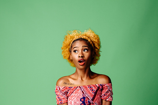 Young Woman With A Shocked Expression Looking At Something Isolated On Green Studio Background Stock Photo - Download Image Now