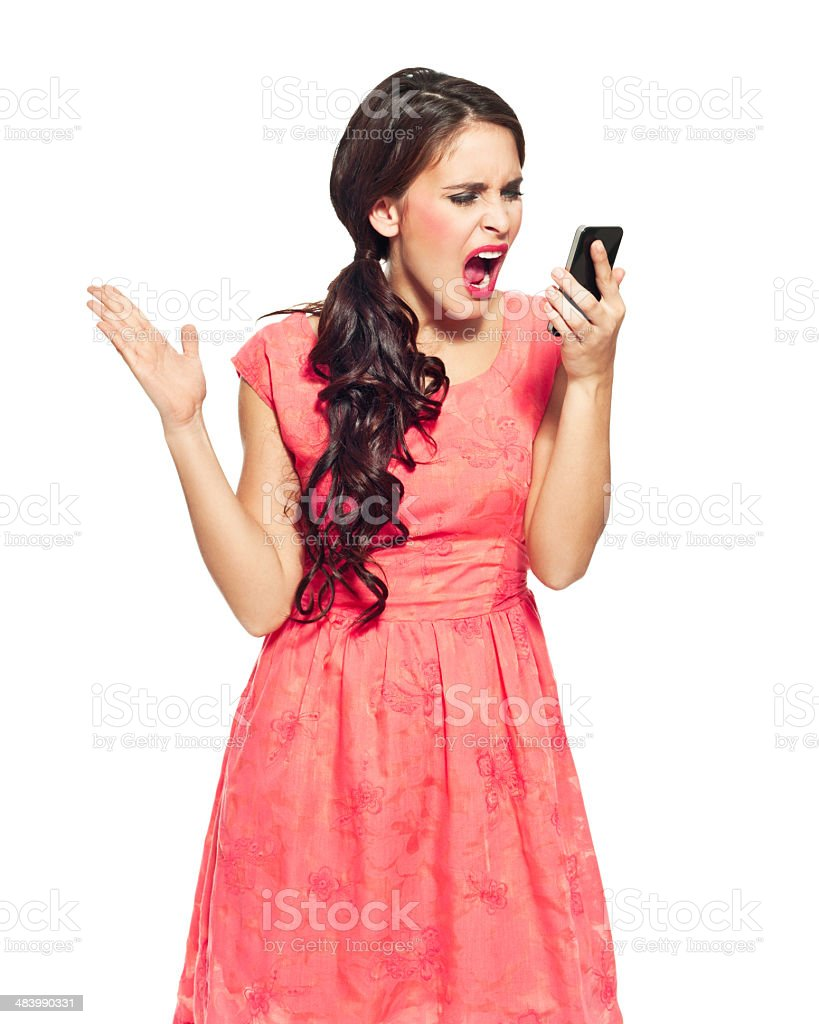 Young woman with a smart phone Portrait of frustrated young woman holding a smart phone in hand and screaming. Studio shot, white background. 20-24 Years Stock Photo