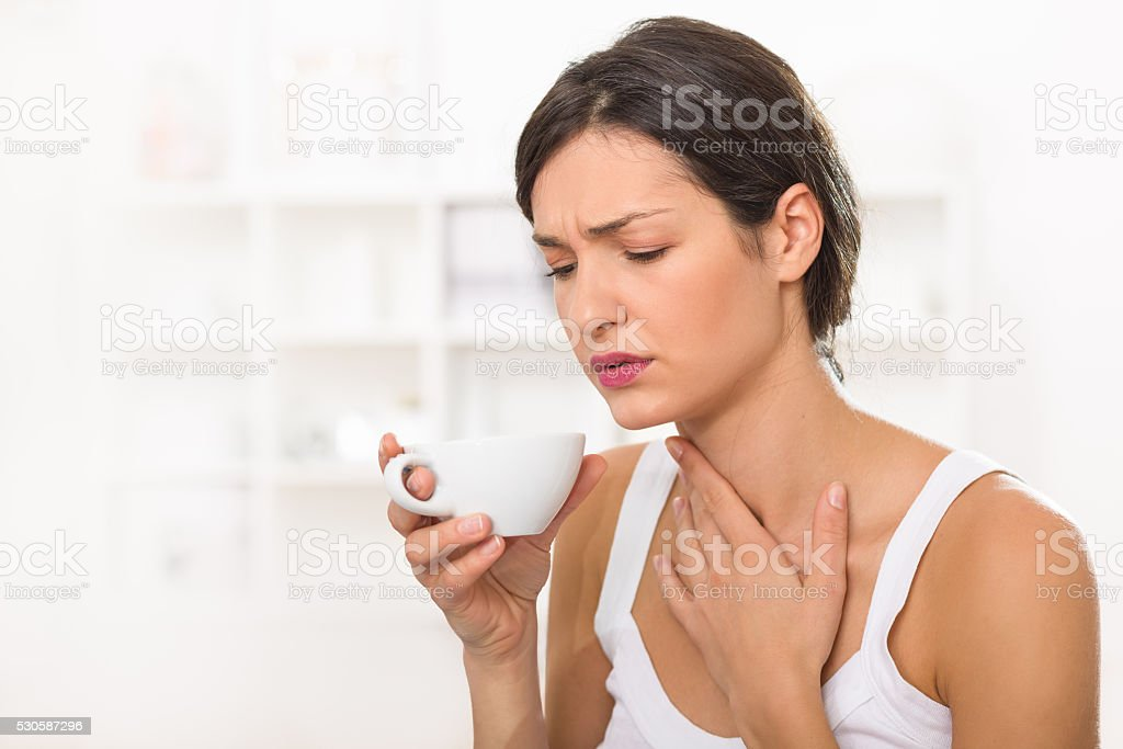 Young woman with a sore throat drinking tea stock photo