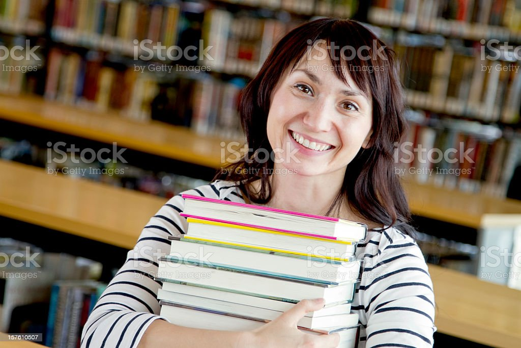 Young Woman with a Stack of Books at the Library royalty-free stock photo