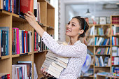 Young woman with a stack of books in library
