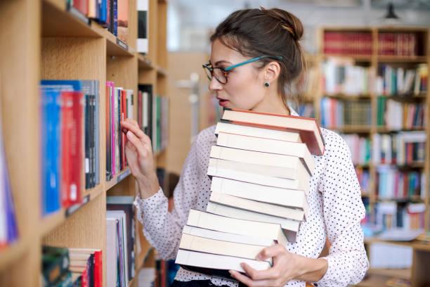 young woman with a stack of books in library want more - политика и правительство стоковые фото и изображения