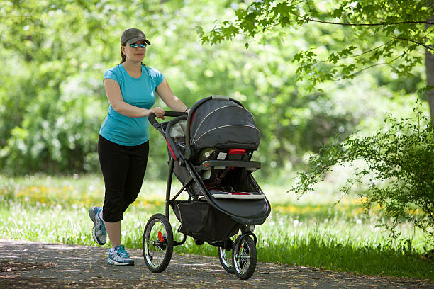 Young woman with a stroller Young mother running while pushing a stroller in the park baby stroller stock pictures, royalty-free photos & images