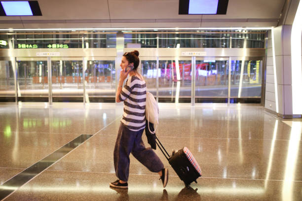 young woman with a suitcase traveling solo on the qatar airport - donna valigia solitudine foto e immagini stock