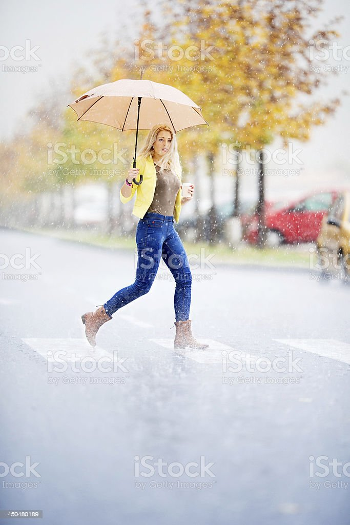 Young woman with a take-away coffee under the rain stock photo