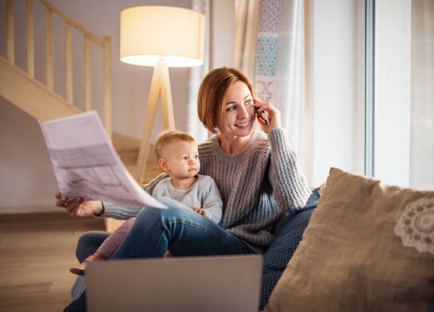 una mujer joven con una hija de niño sentado en el interior, trabajar en casa. - arquitecta fotografías e imágenes de stock