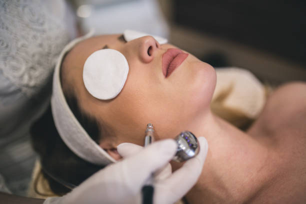 young woman with a towel on her head lying on a table with closed eyes getting a laser skin treatment in healthy beauty spa salon - tattoo removal stock pictures, royalty-free photos & images