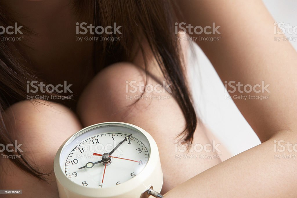 Young woman with a vintage alarm clock royalty-free 스톡 사진