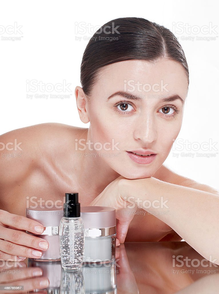 Young woman with  a well-groomed skin near the creams cosmetics. stock photo