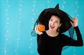istock Young woman with a witch hat holding a halloween pumpkin 1054930552