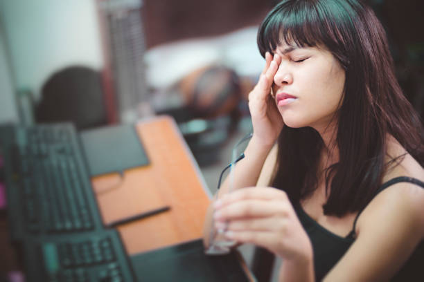 Young woman with aching eyes after working on computer. stock photo