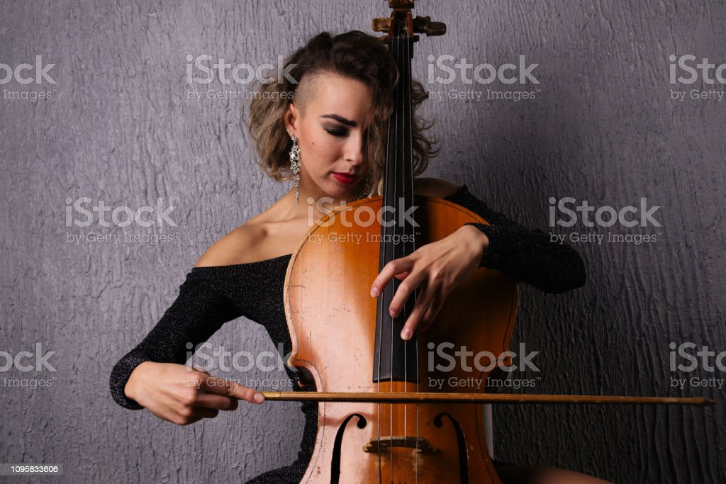 Young woman with acne playing the cello. stock photo