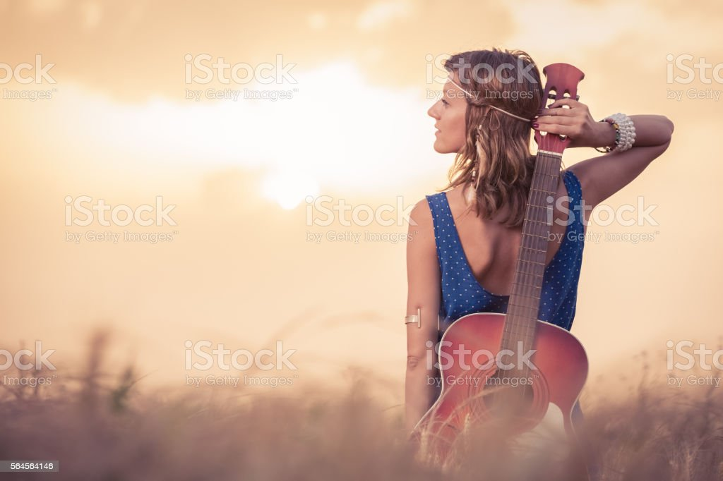 Young woman with acoustic guitar enjoying the sunset stock photo