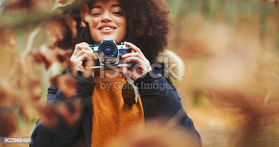 Young woman with afro hairstyle taking photos in the woods