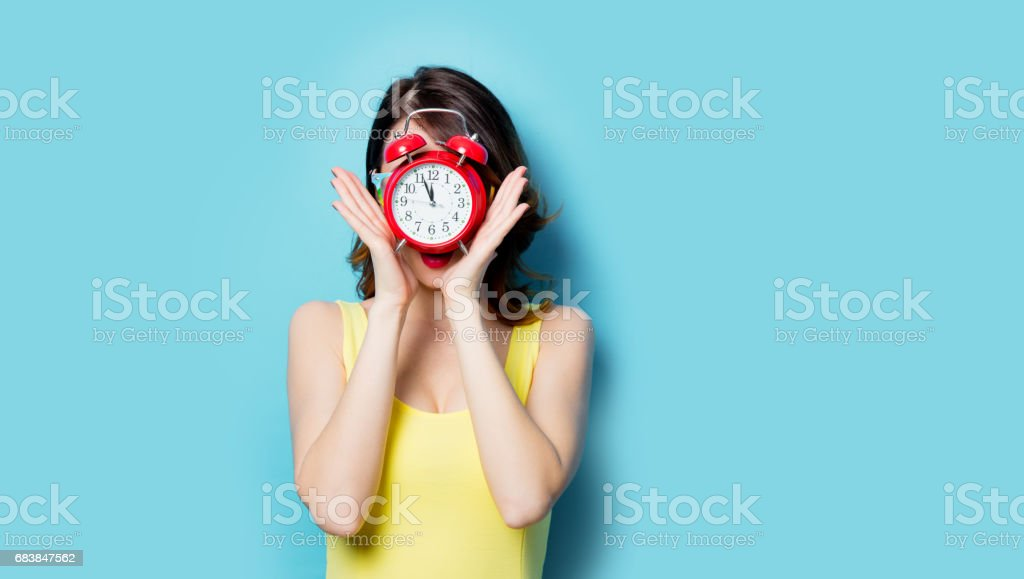 young woman with alarm clock stock photo
