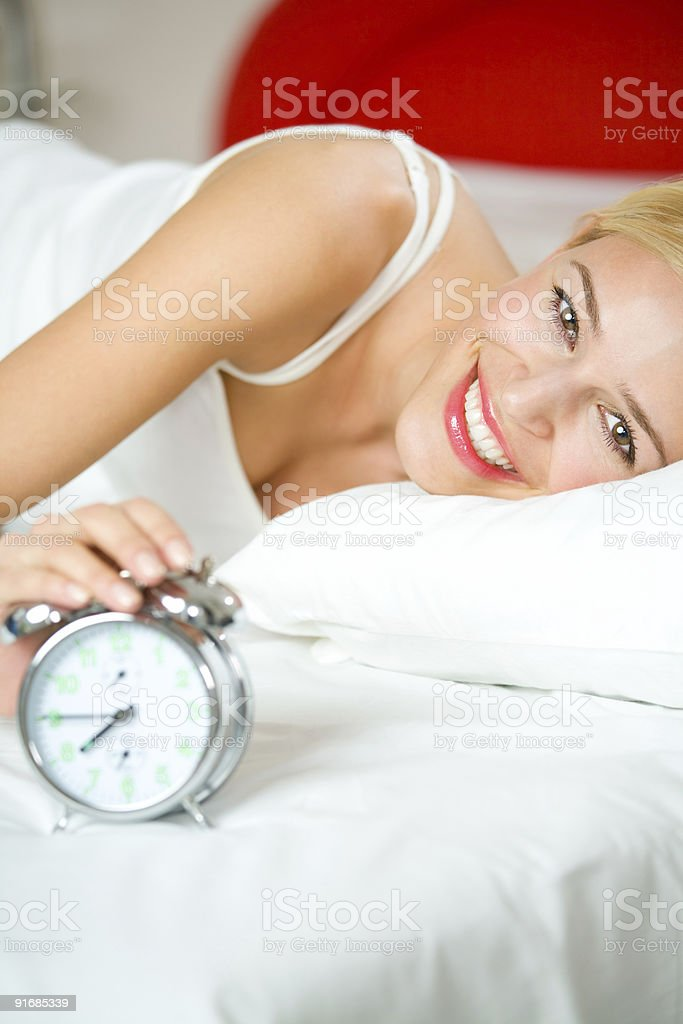 Young woman with alarmclock on bed at morning royalty-free stock photo