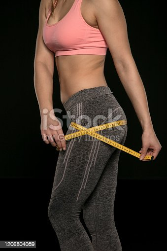 521792745 istock photo young woman with an athletic body uses a measuring tape 1206804059