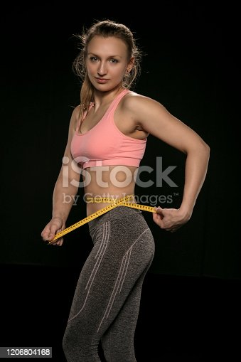 521792745 istock photo young woman with an athletic body uses a measuring tape 1206804168
