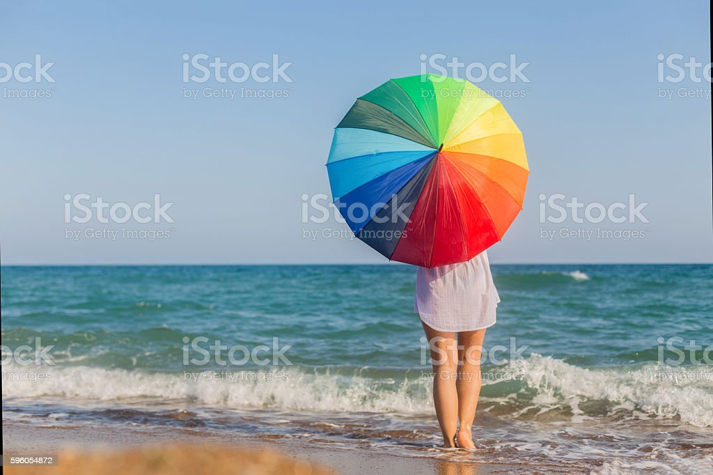 Young woman with an colorful umbrella on the sandy beach royalty-free stock photo