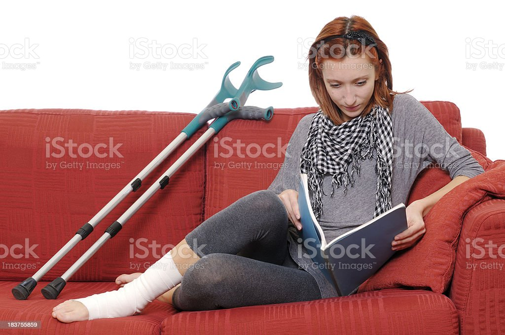 Young Woman with Ankle Bandage Resting on Sofà stock photo