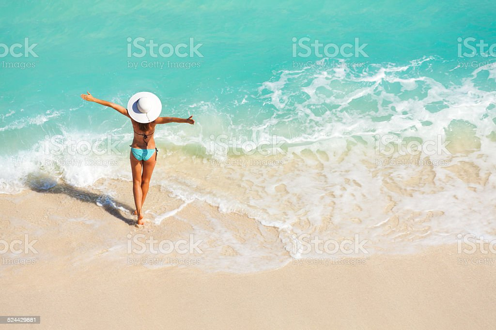Young woman with arms apart with white hat in striped swimsuit...