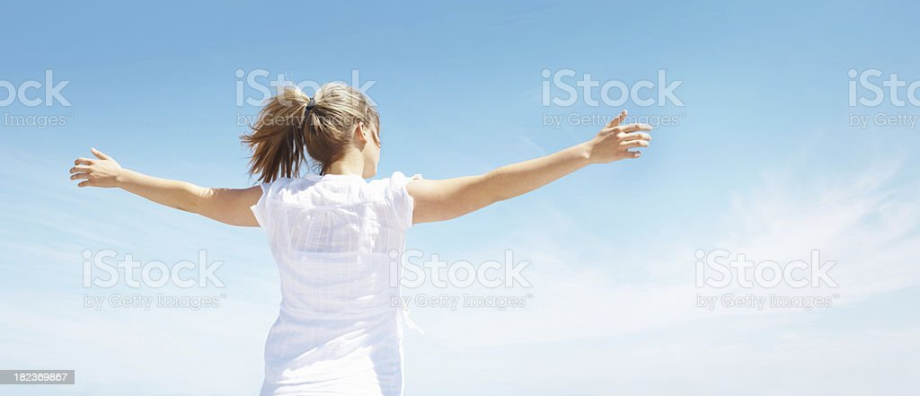 Young woman with arms out , enjoying vacation royalty-free stock photo