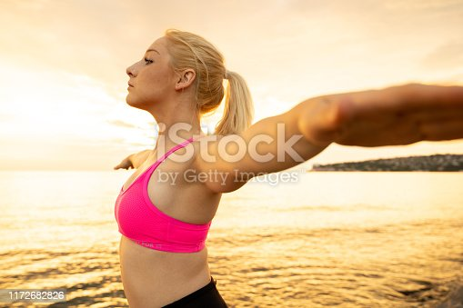 816941230istockphoto Young Woman With Arms Outstretched Standing on Coastline 1172682826