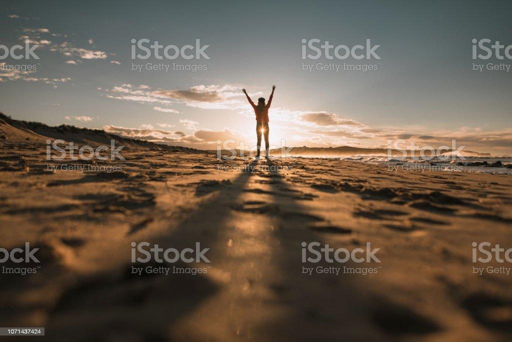 Young woman with arms raised at sunset - Zbiór zdjęć royalty-free (Brązowe włosy)