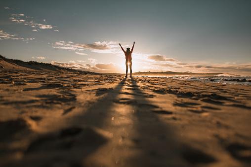 Young Woman With Arms Raised At Sunset - zdjęcia stockowe i więcej obrazów Brązowe włosy