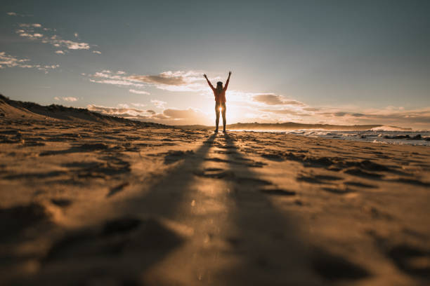 Young woman with arms raised at sunset stock photo