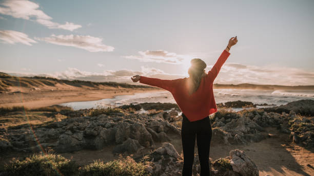 Young woman with arms raised by the sea stock photo