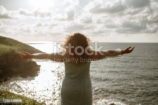Rear view of a young woman with arms raised by the sea