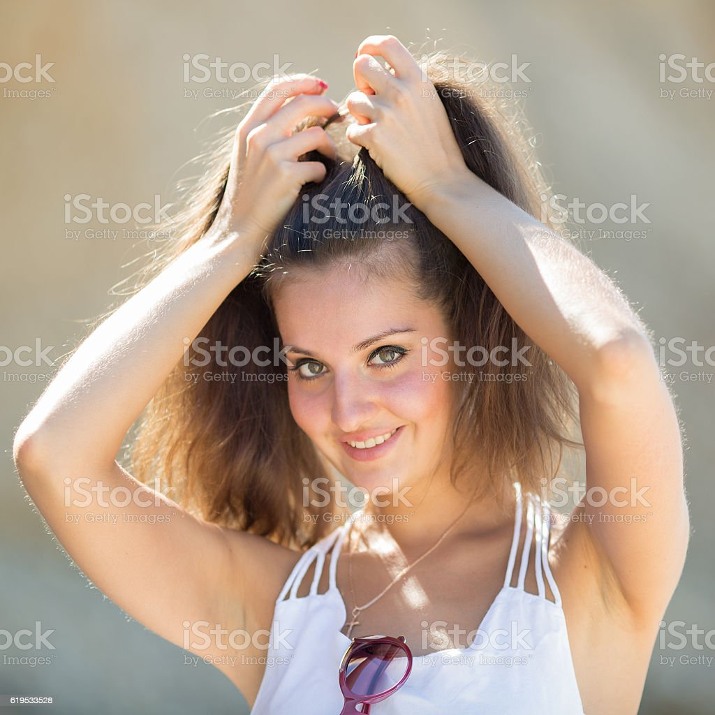 Young woman with arms raised looking at camera stock photo