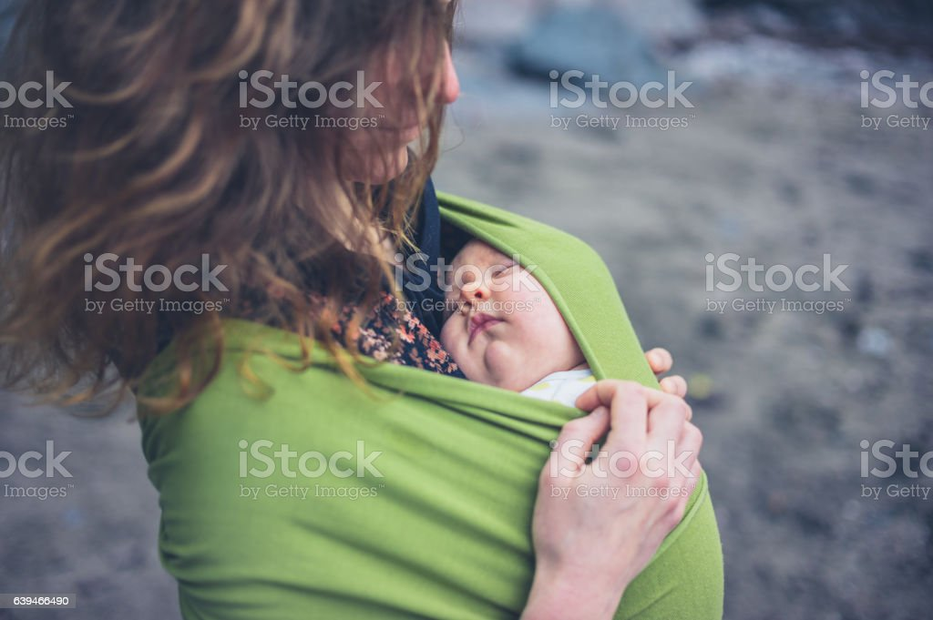 Young woman with baby in sling on beach stock photo
