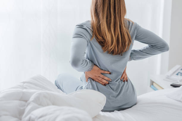 Young woman with back ache, she is sitting on the bed and touching her back stock photo