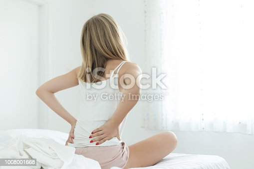 istock Young woman with back pain sitting on bed 1008001668