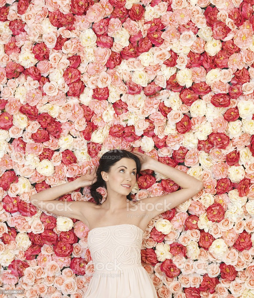young woman with background full of roses stock photo