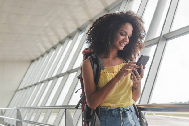 Young woman with backpack checking her boarding schedule at the airport stock photo