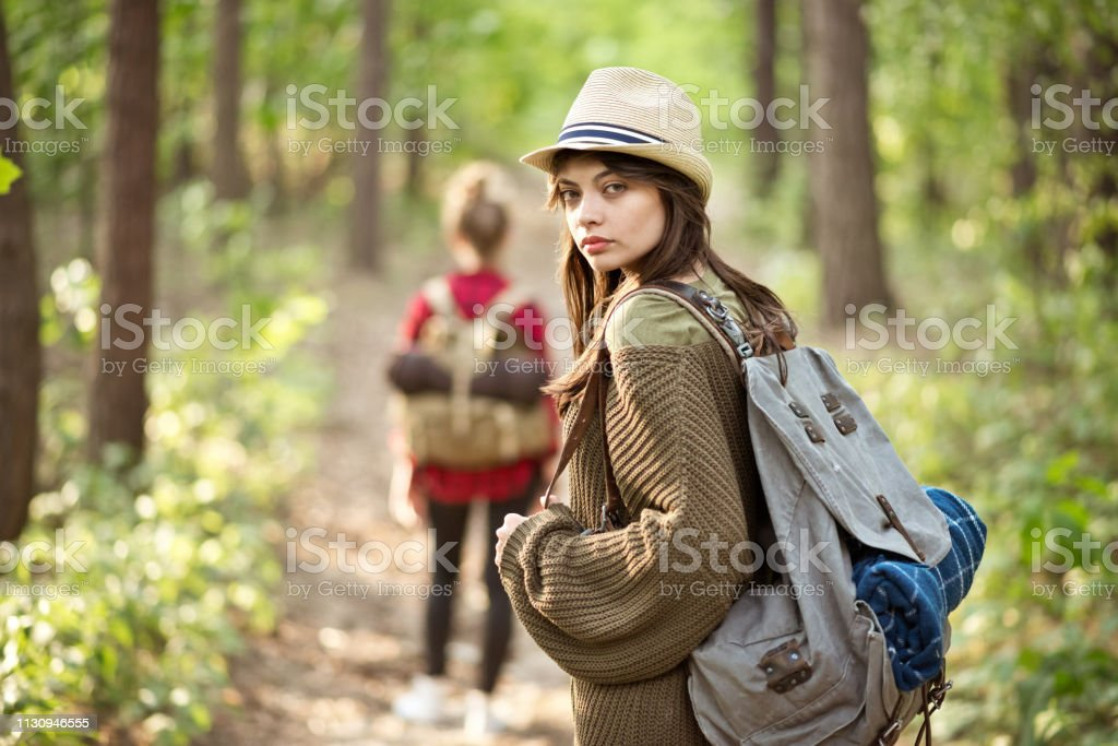 Young woman with backpack hiking in forest Portrait of beautiful young woman hiking with backpack. Female explorer is with friend in forest. They are exploring together during summer vacation. 20-24 Years Stock Photo
