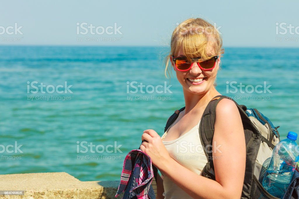 young woman with backpack hiking on sea coast - Royalty-free Adult Stock Photo