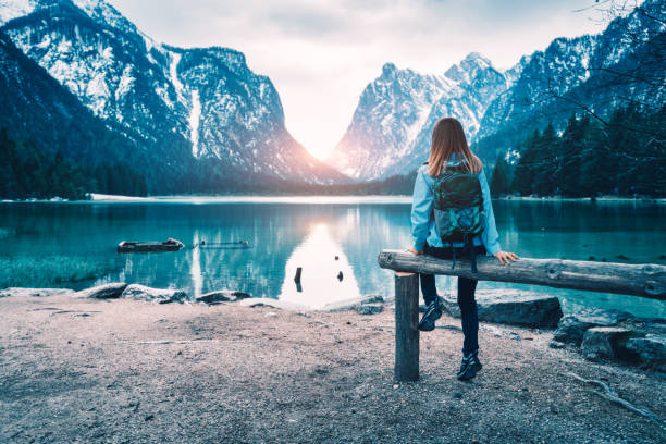 Young woman with backpack is sitting on the coast of mountain lake at sunset in autumn. Travel in Italy in fall. Landscape with slim girl, reflection in water, snowy rocks, green trees. Vintage toning stock photo