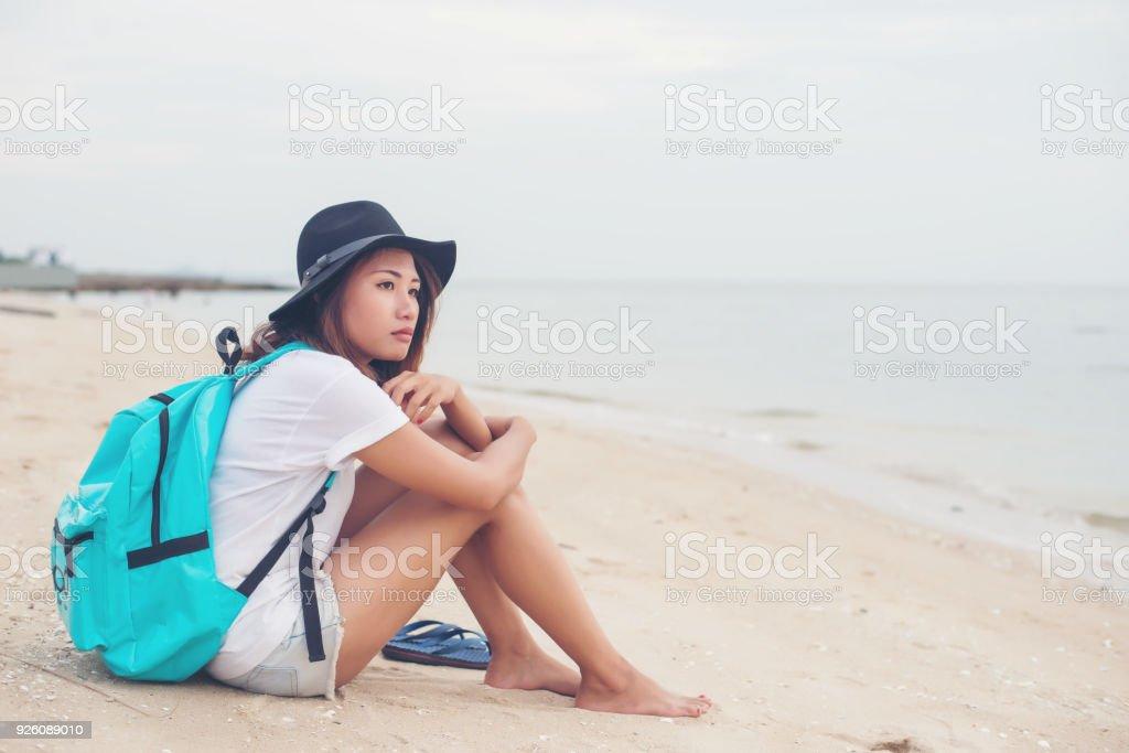 d2507e846 Mujer joven con mochila sentado en la solitaria playa y mirando en la  distancia. foto