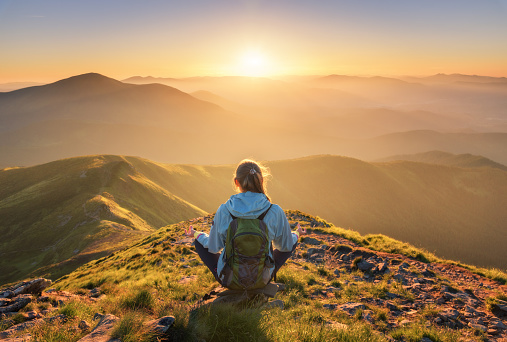 Young woman with backpack sitting on the mountain peak and beautiful mountains in fog at sunset in summer. Landscape with sporty girl, green forest, hills , sky, sunbeams. Travel and tourism. Yoga