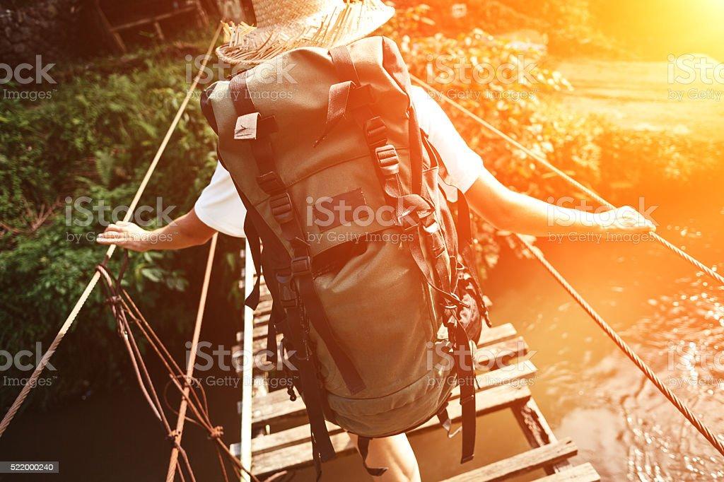 Young woman with backpack walking across danger bridge stock photo
