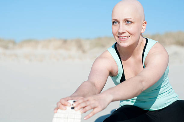 young woman with bald head doing sports after enduring chemotherapy stock photo