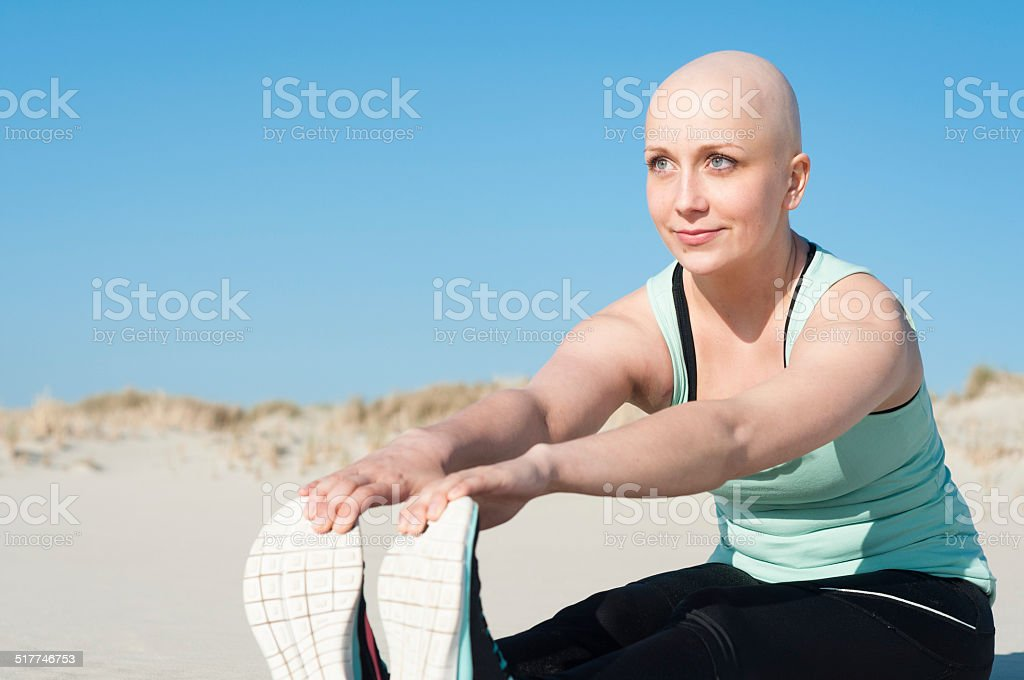 young woman with bald head doing sports stock photo
