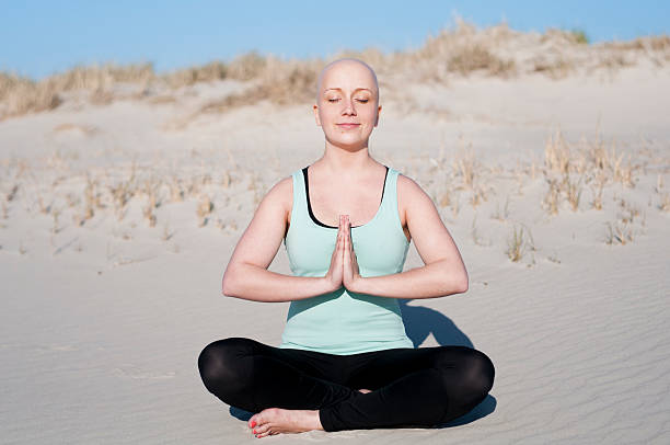 young woman with bald head doing yoga after enduring chemotherapy stock photo